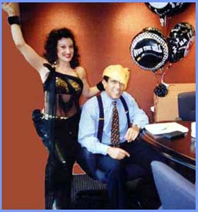 Hire a belly dancer for a belly gram, a belly dancing singing telegram, aka bellygram.  This NYC office hired a bellydance birthday singing telegram to surprise their boss.